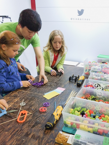 A teacher helping two kids build 3d printed toys on a wooden table with bins of colourful 3D printed parts.